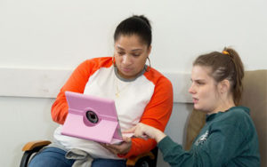 2 girls looking at an ipad.