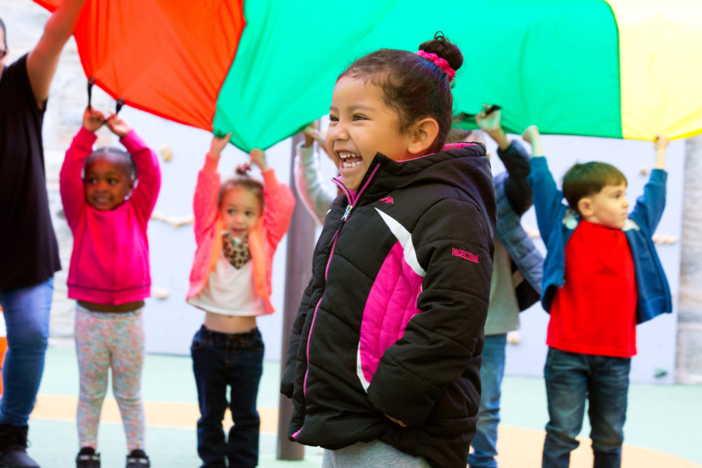 A group of children hold up a rainbow play parachute, one child stands in the center underneath the parachute