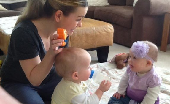 Woman holding up toy to show baby, second baby drinking from a bottle