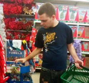 Individual in support program grabbing items from a display of Magic Towels in a grocery store, holding a green shopping basket in the other hand